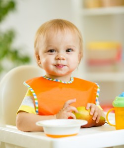happy cute baby kid toddler eating itself with spoon